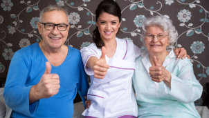 elderly couple and a caregiver doing a thumb's up