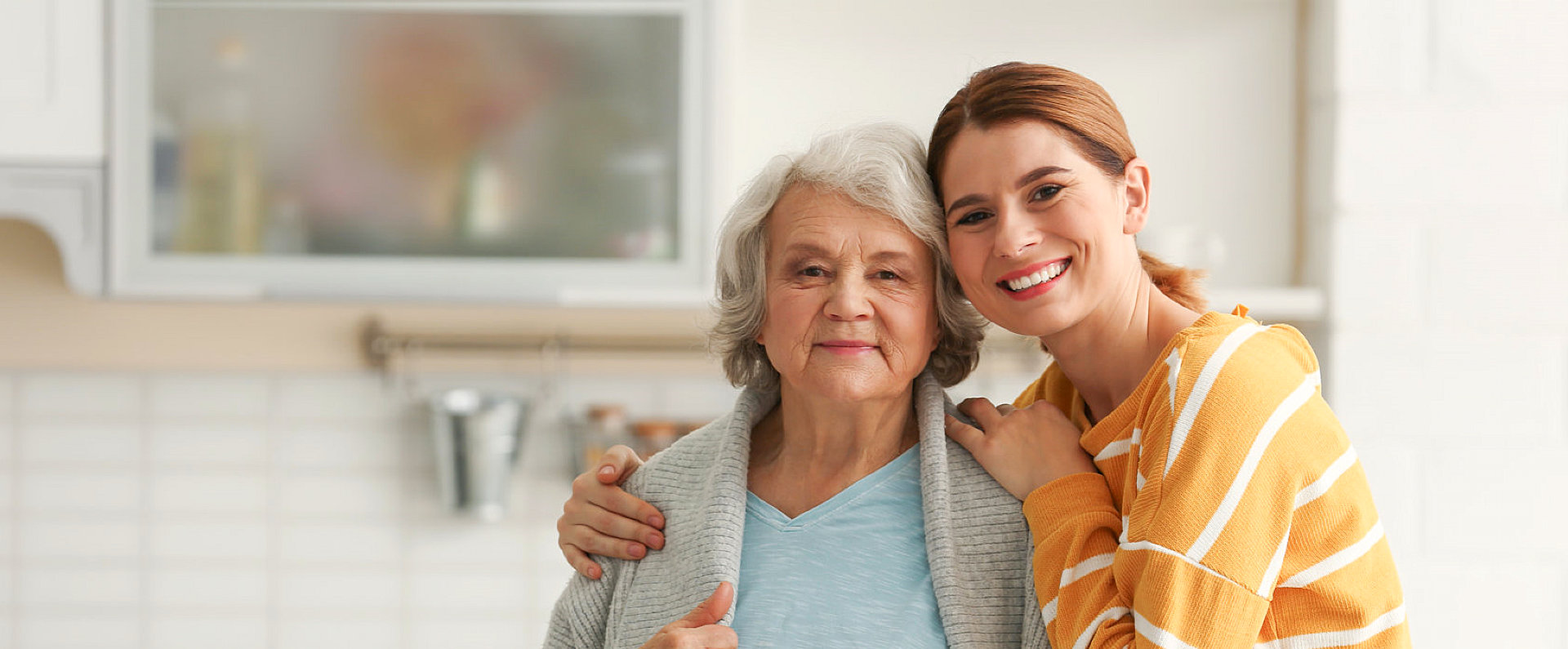 elder woman and her daughter smiling
