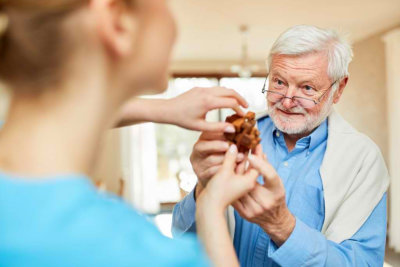 Nursing lady looks after senior men with dementia while playing with the wooden puzzle
