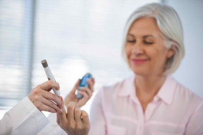 Doctor checking glucose level in diabetic patient in clinic